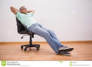 leaning back in chair mature man leaning back swivel chair home living room